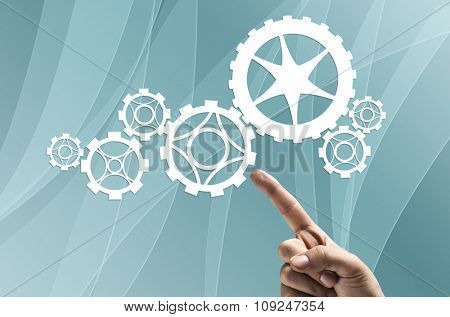 Close up human hand pointing with finger at gears mechanism