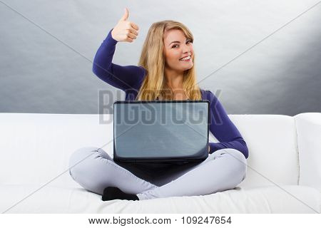 Happy Woman Using Laptop Sitting On Sofa And Showing Thumbs Up