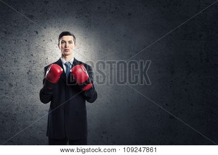 Young businessman in boxing gloves on dark background