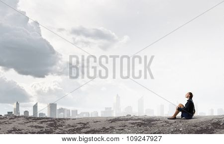 Thoughtful young businesswoman sitting alone on rock top