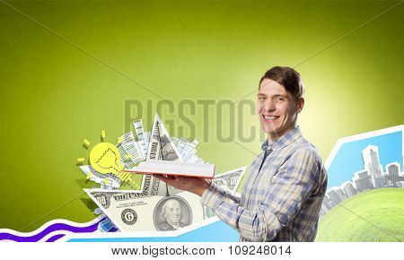 Young man in casual holding opened book with financial concept