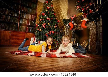 Two cute seven year old children with gifts by the Christmas tree at home. The magic of Christmas.