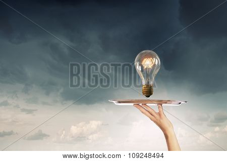 Hand holding tray with glowing light bulb