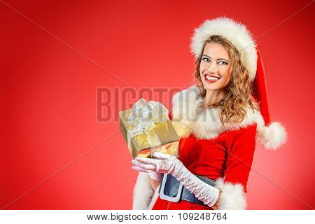 Portrait of a beautiful smiling Christmas girl with a gift box. Red background.