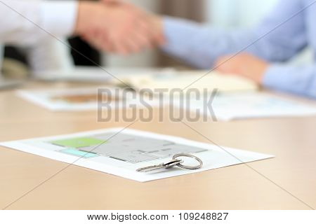 Real-estate Agent Signing A Contract. Handshake.a  House Key With Project Of A Flat Behind.