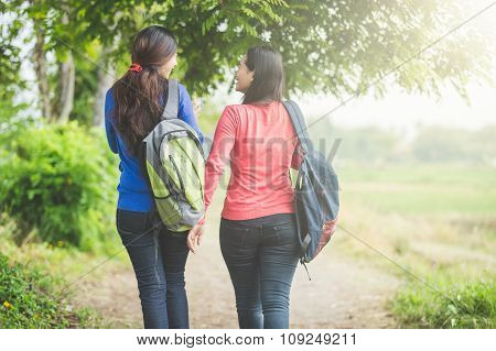 Two Young Asian Students Chatting While Walking Together, Back View