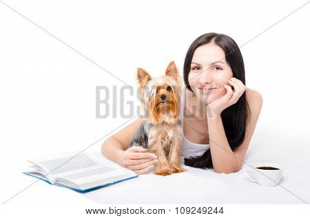 Beautiful young woman with Yorkshire Terrier drinking morning coffee in bed