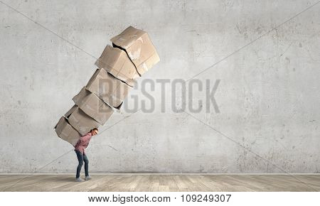 Young girl in casual carrying stack of carton boxes