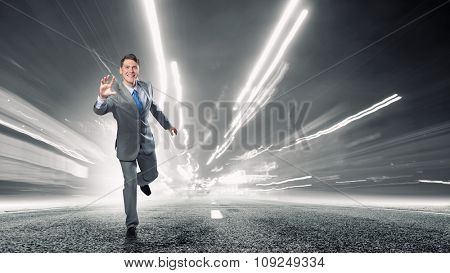 Young businessman in suit running on asphalt road