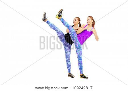 Two athletic girls in sportswear perform stretching exercises. Active lifestyle, healthcare. Twin sisters. Isolated over white.
