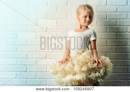Little girl in a tutu by the white brick wall. Ballet school.