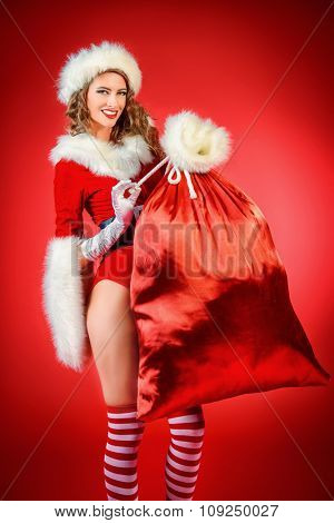 Portrait of a beautiful smiling Christmas girl holding big sack with gifts. Red background.