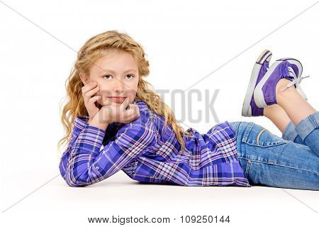 Joyful eight-year girl in casual clothes lying on a floor and smiling. Isolated over white.