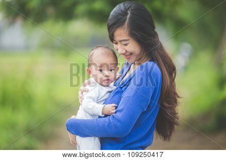 Beautiful Asian Mother Holding Her Baby Daughter