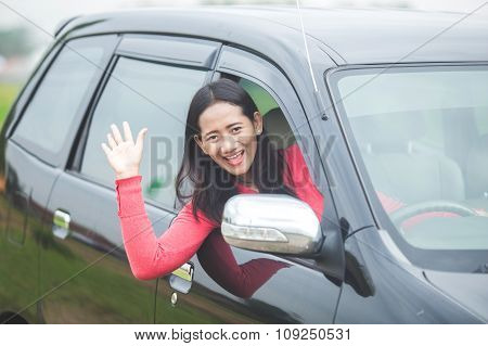 Young Asian Woman Driving A Car, Waving Her Hand Out Of The Window