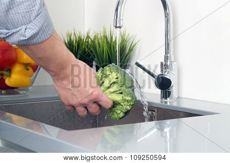 Man  Washing Broccoli   With Water In Kitchen