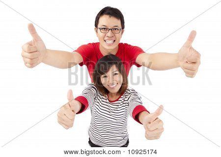 jovem casal comemorando com o polegar até