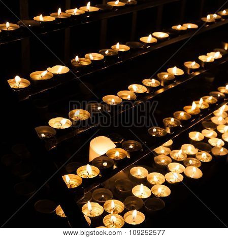 Small Candles Burning In Catholic Church