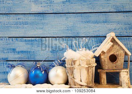 Birdhouse And Christmas Decoration On Blue Background.