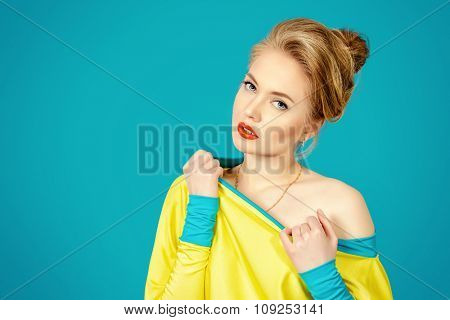 Beautiful fashion woman alluring in vivid colourful clothes over blue background. Bright fashion. Studio shot.