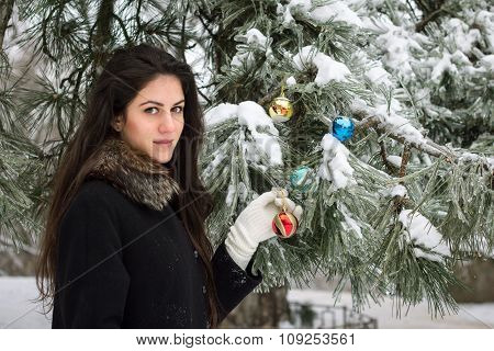 Girl Decorates A Fir Tree
