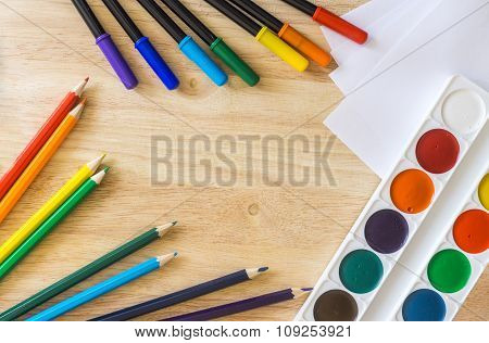 Colored Felt-tip Pens, Pencils, White Paper And Watercolor On Wooden Background
