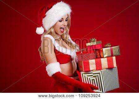 Beautiful Girl with Christmas gift over Xmas background.