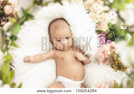 Adorable Little Baby Girl On Fur Blanket With Flowers