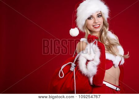 Christmas, x-mas, winter, happiness concept - smiling woman in santa helper hat with many gift boxes. Cheerful santa helper girl
