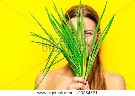 Joyful young woman with green onion over summer yellow background. Healthy food.