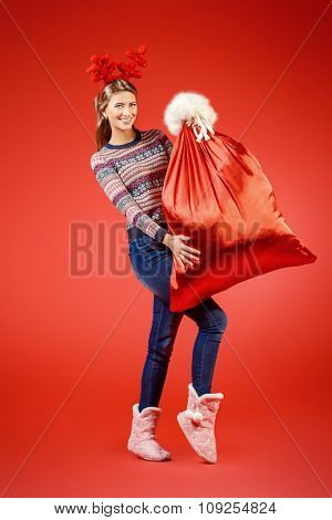 Beautiful happy young woman wearing Christmas deer horns holding big sack of Santa Claus with gifts. Christmas celebration. Shopping. Full length portrait.