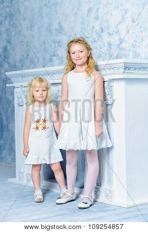 Two angelic sisters in white dresses standing together by the fireplace. Romantic vintage style.