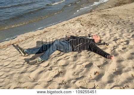 Happy Man Relaxing On The Beach, Lying On The Sand, Smiling, Looking At The Sky And Enjoying Life