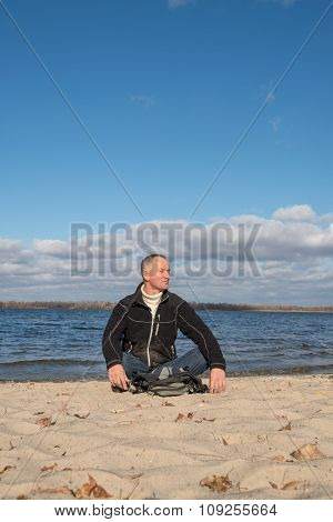 Hiker Man Sitting On The Beach, Smiling, Relaxing And Enjoying Life