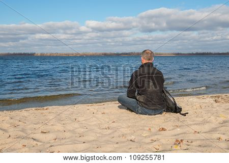 Hiker Man Sitting On The Beach, Back To Camera, Relaxing, Thinking About Something