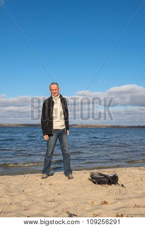 Hiker Man Standing On The Beach, Smiling And Having Fun On The Background Of The Blue Sky