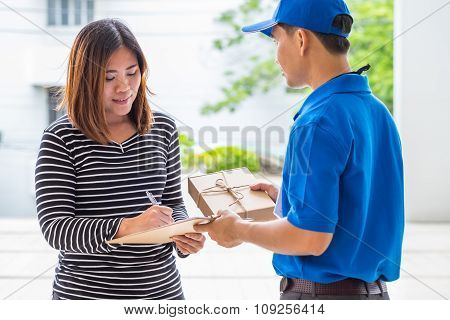 Asian Woman Signing Receipt Of Delivered Package