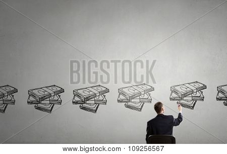 Rear view of businessman drawing with marker money earning concept