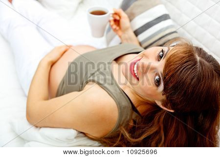 Smiling beautiful pregnant female relaxing on sofa with cup of tea in hand. Close-up.