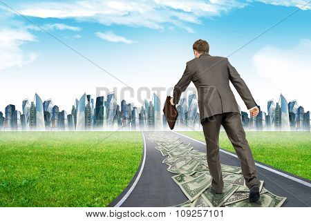 Man with suitcase on money road