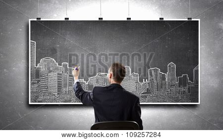 Rear view of businessman drawing construction project on banner