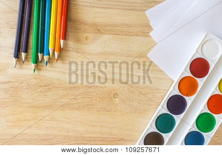 Colored Pencils, Lying Like Rainbow, White Paper And Watercolor On Wooden Background