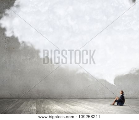 Bored young businesswoman sitting alone on floor