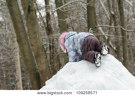 Toddler girl climbing top of snowy hill in winter park