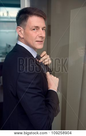 Man In Suit Binding His Tie