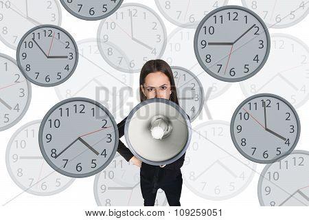 Businesswoman scream to megaphone among clocks.