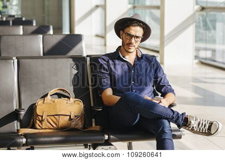 Young traveler sitting in an airport, with a leather briefcase and his smartphone