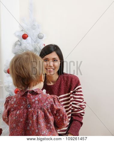 Portrait Of Happy Mother And Her Baby From The Back Having Fun Near Christmas Tree