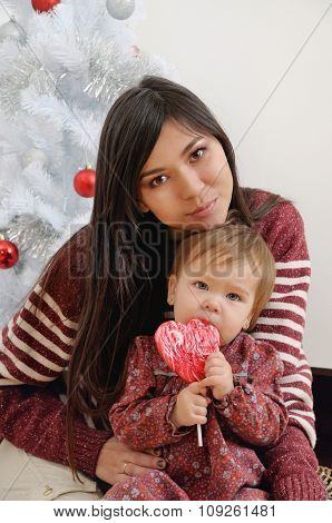 Portrait Of Happy Mother And Her Baby Near Christmas Tree