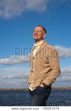 Happy Smiling Man, Wearing Casually, Walking Along The Coast In Magic Autumn Day And Enjoying Life
